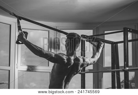 Mens Heals Body Care. Man With Torso, Sportsman, Athlete, Muscular Macho Does Exercise With Trx Loop