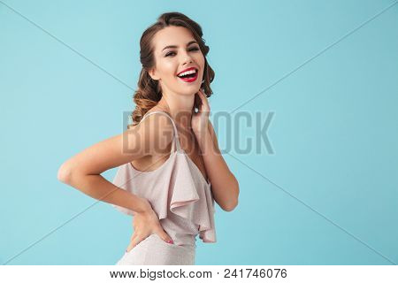 Image of happy brunette woman 20s wearing party outfit smiling at camera with white teeth isolated over blue background poster