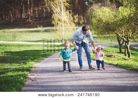 A Father With His Two Toddler Children Outside On A Sunny Spring Walk.