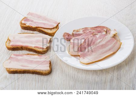 Three Sandwiches With Bacon, Plate With Slices Of Bacon On Wooden Table
