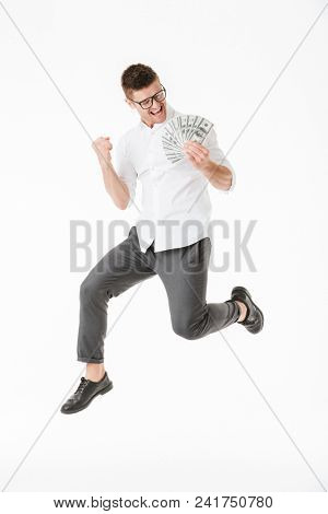 Full length portrait of a happy young man in eyeglasses holding money banknotes and jumping isolated over white background