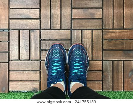 Selfie Of Feet With Blue Sneaker Shoes On Wooden Tile And Grass Floor, Top View