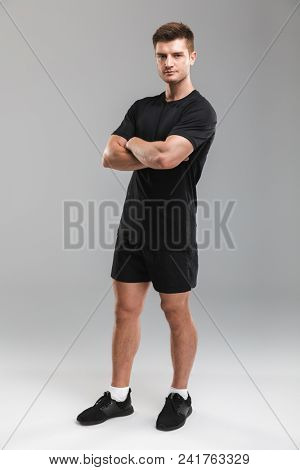 Full length portrait of a confident young sportsman standing with arms folded isolated over gray background