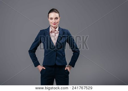 Smiling Adult Businesswoman With Hands In Pockets Looking At Camera Isolated On Grey
