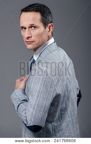Handsome Adult Businessman In Stylish Suit Turning Back And Looking At Camera Isolated On Grey