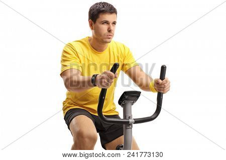 Young man exercising on a stationary bicycle isolated on white background poster