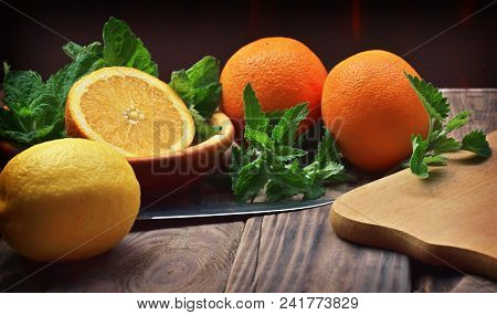 Preparation Of A Refreshing Drink From Ice Water, Fruits And Mint, Lemon Balm. Fruits Close-up. Oran