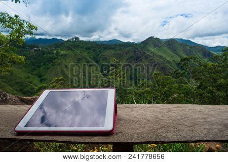 Digital Tablet On The Wooden Desk With View On Mountain. Using Modern Device During Vacation