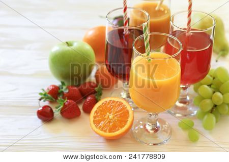 Variety Of Fruit Juices In Four Glasses Orange Juice, Cherry Juice, Mix Juice Of Apple, Apricot, Pea