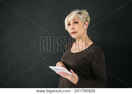 A Successful Positive Modern Elderly Woman Holds A Tablet In Her Hands And Uses It. The Older Genera