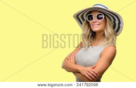 Young woman wearing sunglasses and summer hat with crossed arms confident and happy with a big natural smile laughing