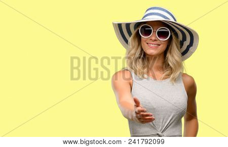 Young woman wearing sunglasses and summer hat holds hands welcoming in handshake pose, expressing trust and success concept, greeting
