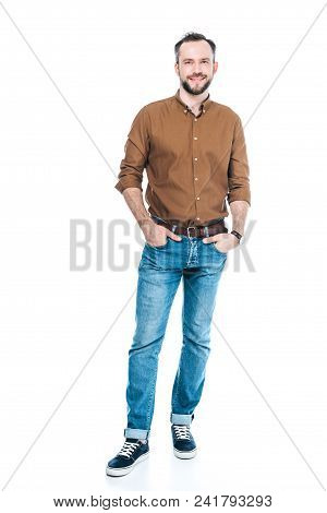 Full Length View Of Handsome Bearded Man Standing With Hands In Pockets And Smiling At Camera Isolat