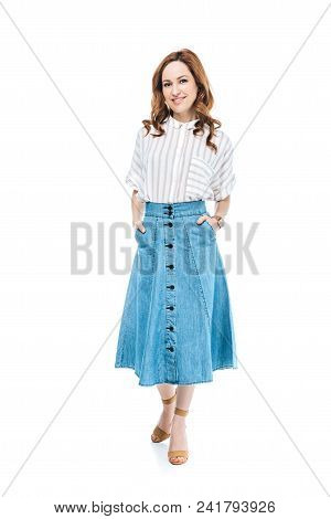 Full Length View Of Beautiful Woman Standing With Hands In Pockets Of Denim Skirt And Smiling At Cam