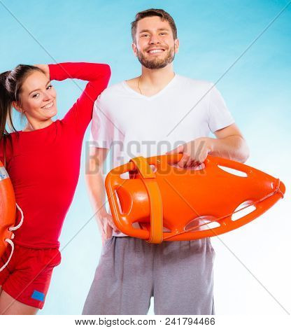 Accident Prevention And Water Rescue. Lifeguard Couple On Duty Woman Leaning On Man Arm, Holding Buo