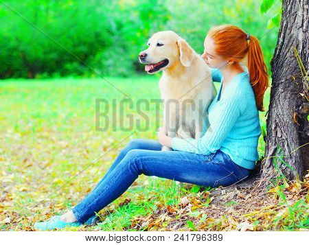 Owner Woman And Golden Retriever Dog Together Is Sitting Near A Tree In The Park
