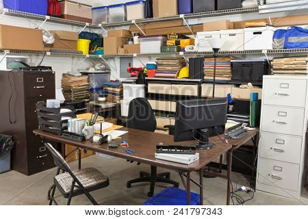 Busy messy back office with piles of files and storage boxes.