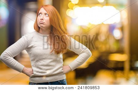 Beautiful young redhead woman doubt expression, confuse and wonder concept, uncertain future at night