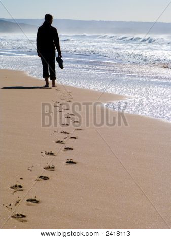 Woman Walking Alone At The Beach