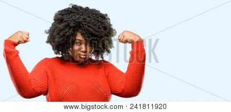 Beautiful african woman showing biceps expressing strength and gym concept, healthy life its good, blue background