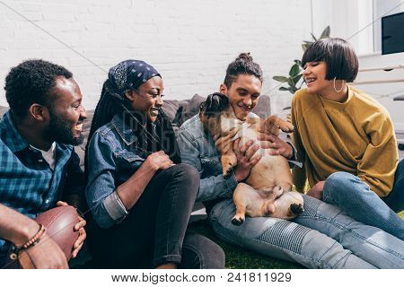 Group Of Smiling Young Multicultural Friends With French Bulldog
