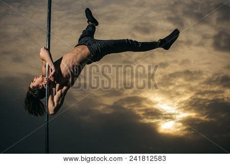 Pole Dance Sport. Young Muscular Man Dancing On Pylon In Sunset. Athletic Guy Make Acrobatic Element
