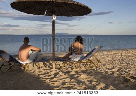 Couple on vacation or honeymoon. Man and woman topless enjoy view on sea, rear view. Couple in love at sea resort sits on loungers under umbrella on sand beach. Honeymoon concept. poster