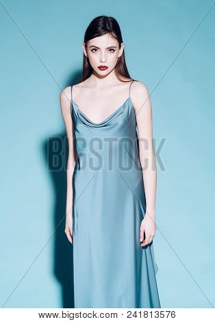 Beautiful Girl In Icy Blue Fluttering Atlas Dress Isolated On Blue Background. Brunette Teen Posing