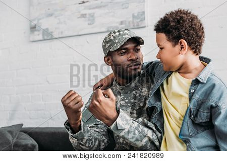 Father In Army Uniform And African American Boy Embracing And Talking At Home