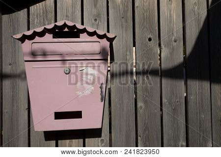 Vintage Metal Mailbox On A Wooden Fence Wall Made Of A Brown Board.