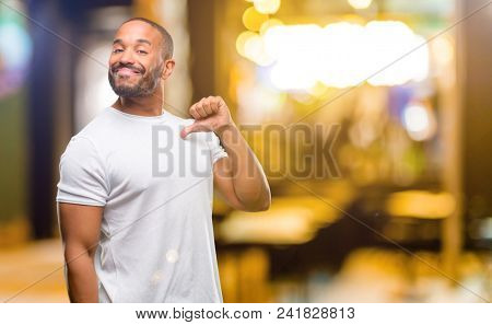 African american man with beard proud, excited and arrogant, pointing with victory face at night