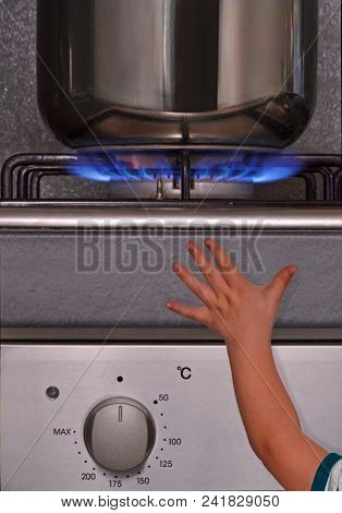 Child approach hand to a burner gas stove top in the kitchen.