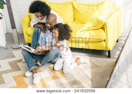 African American Family Reading Book Together At Home