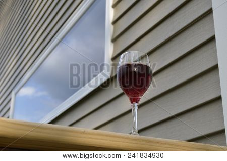 Red Wine In A Glass On The Outdoor Deck Railing