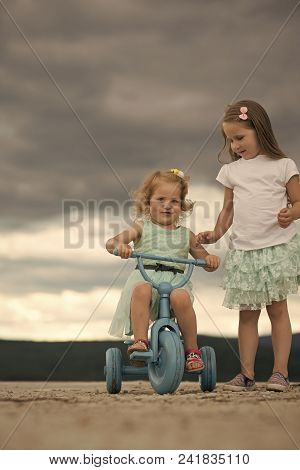 Child Childhood Children Happiness Concept. Girl Ride Tricycle With Sister On Cloudy Sky. Children P