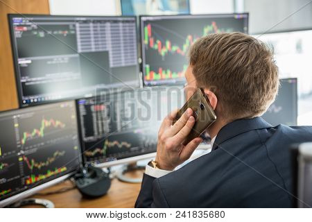 Over The Shoulder View Of And Stock Broker Trading Online While Accepting Orders By Phone. Multiple