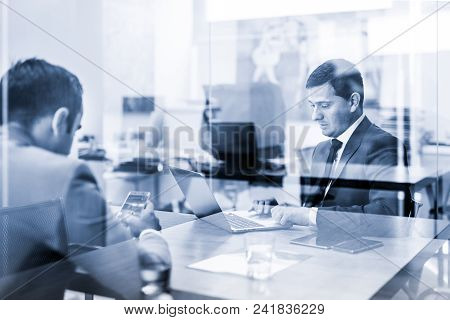 Through The Window View Of Two Young Businessmen Using Laptop Computer And Smart Phone Devices At Wo