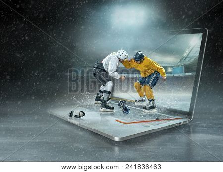 Caucassian ice hockey Players in dynamic action boxing in a professional sport game play on the laptop in hockey under stadium lights.