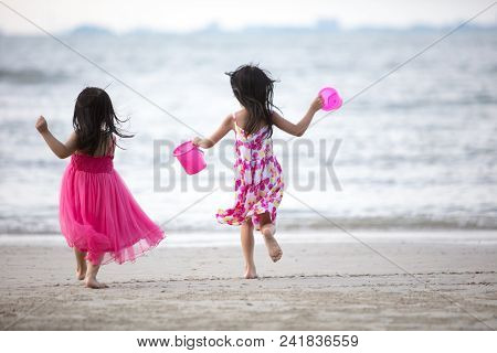 Asian Chinese Little Sisters Having Fun At Beach Outdoor