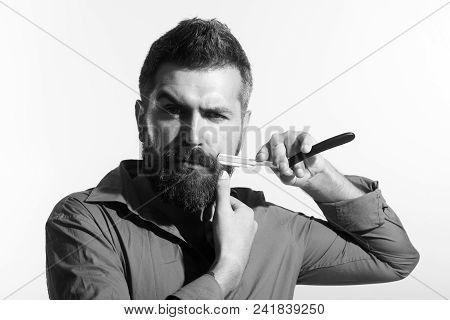 Bearded Man Having Shave In Barbershop With Razor Blade. Professional Barber Holds Straight Razor Ne