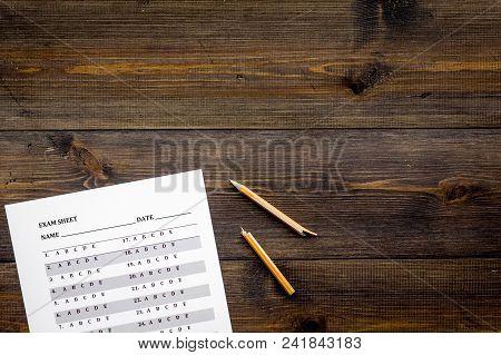 Exam Sheet On Dark Wooden Table Top View Copy Space. Education Concept. Exam Problems. Broken Pencil