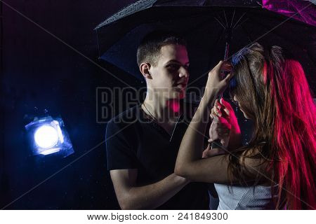 Couple Young Teens Stand Together With Black Umbrella And Colored Light Behing