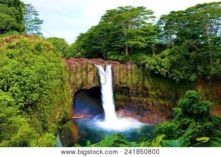 Rainbow Falls Which Is A Large Waterfall Over A Bluff Surrounded By A Tropical Rain Forest Taken In