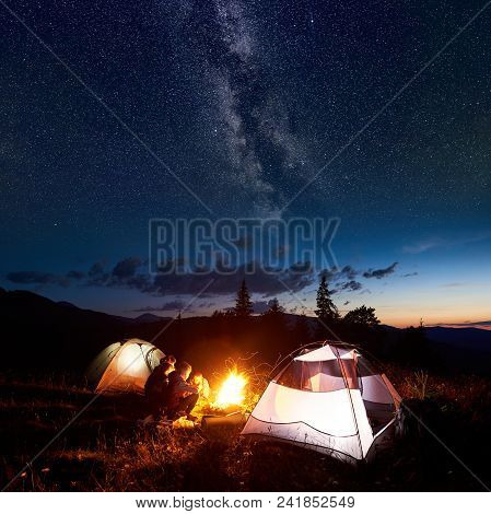 Family Hikers Mother, Father, Two Sons Having A Rest At Night Camping In Mountains, Sitting On Log B