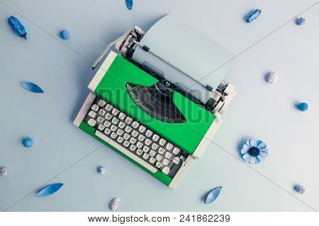 Flat Lay Of Green Retro Typewriter Against Blue Flower Pattern Background Minimal Creative Concept.