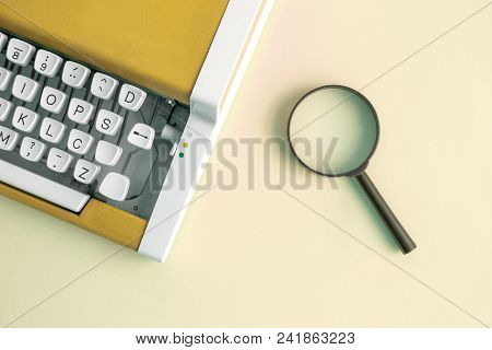 Flat Lay Of Vintage Typewriter In Yellow Color And Magnifying Glass Minimal Creative Concept.