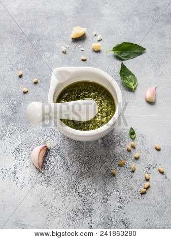 Ingredients For Pesto And Sauce In White Mortar  Made From Green Basil, Garlic, Pine Nuts, Parmesan