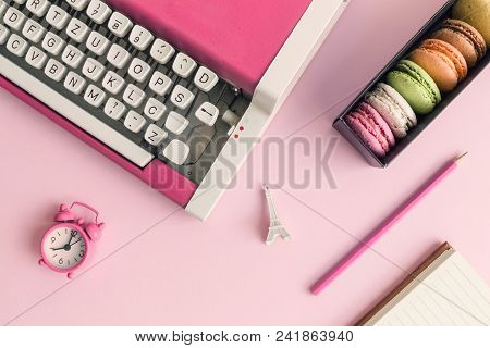 Flat Lay Of Typewriter, Macaroons, Alarm Clock, Eiffel Tower Miniature And Notebook With Pencil Pink