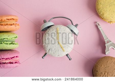 Flat Lay Of Colorful Macarons And Eiffel Tower Miniature Model On Pastel Pink Background. One Of Mac