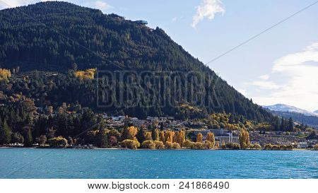 The Shoreline Of Queenstown In New Zealand As Seen Across The Water Of Lake Wakatipu.  The Season Is